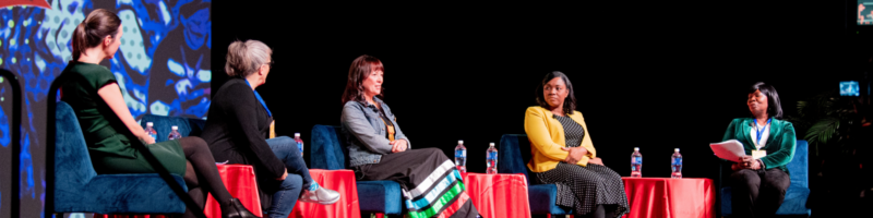 5 women on a stage in a panel-style format.